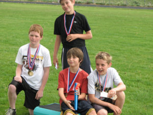 Members of the boys' 4x100 relay team in the 11-12 age group received medals for their winning effort. From left, Jacob Phelan, Jake Nielsen (standing), Sam Nieslanik and Jacob Henderson.