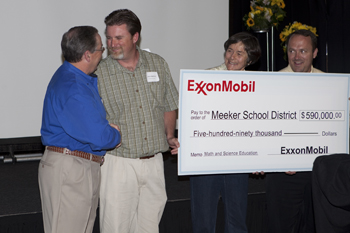 Jason Hightower, second from left, principal of Meeker Elementary School, is congratulated by ExxonMobil executive Jim Branch after the presentation of a $590,000 gift to the Meeker School District.