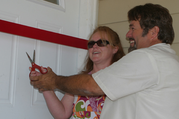 Pastor Roger Barnes and his wife, Anisa, prepare to cut the ribbon at the entrance of their new home. They have three children, ages 18, 16 and 13.