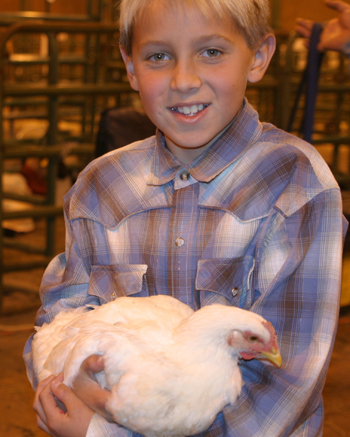Ketsen Rouse of Rangely holds his champion chicken. See inside for a complete listing of fair results. Results of the horse show will publish in next week's Herald Times.