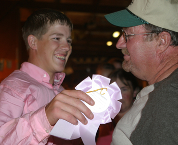Trey Morris receives congratulations from his grandfather Gerald Morris after winning reserve champion market swine at the Rio Blanco County Fair.