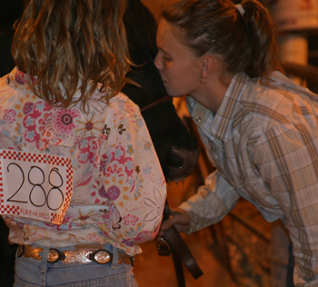 Shelby Burke gives a good-luck kiss before entering the livestock arena while showing during the county fair.
