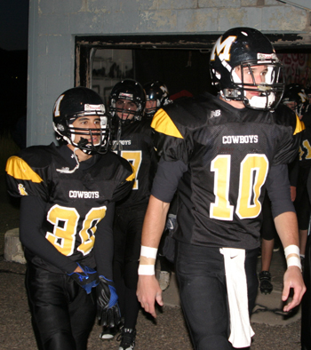 Toby Casias, left, and Colton Brown lead the Cowboys out of the locker room to take the field before Friday's homecoming game.