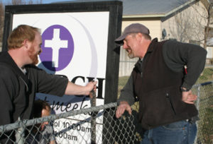 John Brown, left, Bob Lange, right, and Burnie Cox, kneeling, helped take down the sign for The Church at Meeker on Sunday as part of the church's move to a new meeting place on the west side of town.