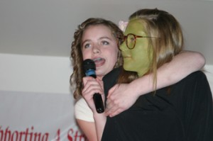 "McKenna Kummer sang a song from the Broadway musical ""Wicked,"" with assistance from Reagan Pearce, during the talent show at last week's Meeker Chamber of Commerce annual banquet."