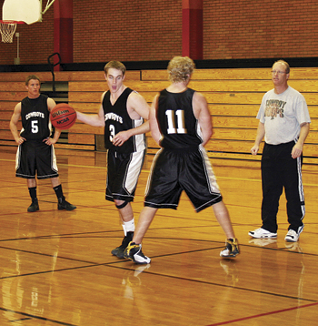Meeker High School boys' basketball coach Klark Kindler works with seniors Cole Steiner (5), Jake Nieslanik (3) and Ryan Wix (11) during a recent practice. The Cowboys will open the 2010-2011 season this Friday in Aspen.