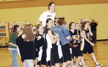 Barone Middle School eighth-graders carry their coach Kris Casey on their shoulders to receive their trophy for winning the league tournament, held last week at Meeker's new elementary school.