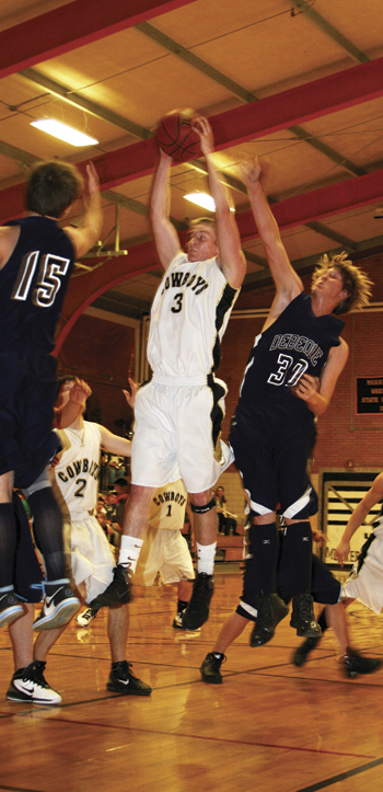 Senior Jake Nieslanik pulls down a rebound between two DeBeque defenders last week. The Cowboys will play DeBeque again Friday and will host Plateau Valley Saturday.