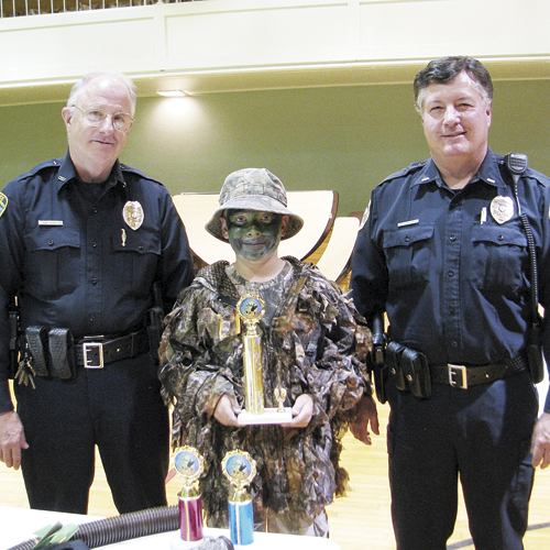 Meeker Chief of Police Bob Hervey and Lieutenant Phil Stubblefield stand with Kesston Hobbs, the overall grand champion of the elk bugling and camouflage competition.