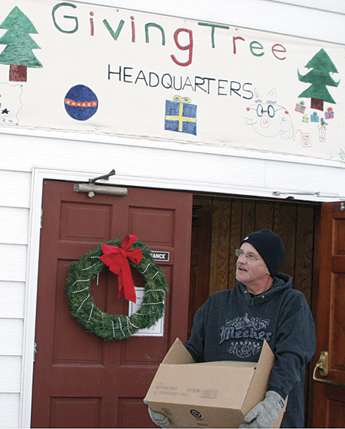"Pastor Johnny Arrington helping out with the Giving Tree distribution at the United Meeker Methodist Church. He and his wife Patti consider themselves ""blessed"" to be able to give back to the community through the Giving Tree, which Patti helps to spearhead."