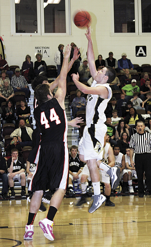 Meeker junior Scott Smith goes up for a shot over Del Norte's Zack Sanchez in the first round game of the regional tournament, which Meeker won last Friday at Colorado Mesa University. Smith led the Cowboys in scoring with 13 points against the Tigers and scored seven in the championship game against the Lutheran Lions, which Meeker lost, ending their season as league and district champions with a 21-2 record.