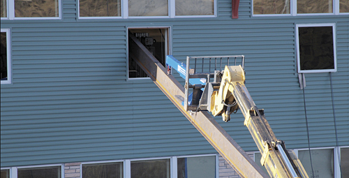 A large beam is successfully lifted into a window on the second floor of the new elementary school. It was reported that the repairs are on schedule for a summer completion.
