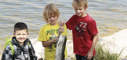 Xavier Preciado is pictured with twins Andrew and Anthony Dorris and the 22-inch trout caught by Andrew.