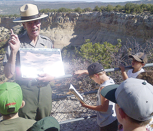 Ranger Randy explains to junior rangers how the Dinosaur National Monument was formed.