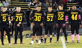 Referee Mike Bullen leads Meeker High School senior captains Nate Walsh, J.R. Crawford, Fernando Olivas, (Austin Brown behind Olivas) Adrian Shoyer, Alex Smith, Tala Atoafa and Scott Smith, out for the coin flip before the 2012 homecoming game against the Paonia Eagles. The grandstands at Starbuck Stadium later cheered on the Cowboys in an exciting game they fought hard to win, yet lost by one point. Meeker will play in Cedaredge this Friday.