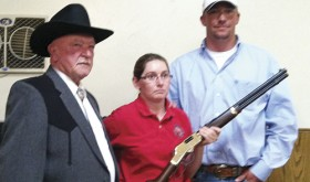 Maryann Hansen accepts the Henry Golden Boy rifle she won at Friday's Elks Charity Ball auction. The rifle was donated by Crossfire Oil and Gas Construction Services and the raffle raised $2,500 for Elks charity projects.