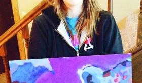 Rangely High School sophomore Jess Tolley holds her painting of a snow leopard, which was chosen to be included in the annual Celebrating Art publication last year. Tolley's pencil drawing of an angel was selected for this year's publication.