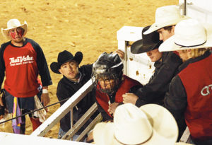 Former RBC graduates Tyler Williams (bullfighter) and Justin Steele (chute operator) wait for CNCC bull rider Tyler Orchard to nod his head, as teammates Brice Osborne and Coty Cornia (both in white cowboy hats), give him encouragement. Orchard didn't make the full ride, but Osborne and Cornia did and split first place in the long go before tying for first place overall in the bull riding event.