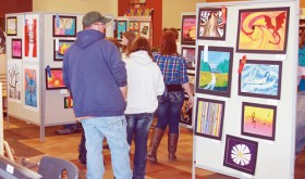 Visitors check out some of the art work displayed at the Meeker Elementary School as part of the Meeker High School Spring Art Show and Coffee House. The coffee house was held to showcase the MHS students' performing arts, and talents included singing, instrumentals, poetry, dance and humor.