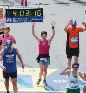 """Sarah Ward of Rangely (pink shirt with sunglasses) crosses the finish line with an unofficial time of 4:03.16 and an official time of 3:57.46. She finished the race several minutes before two bombs detonated near the finish. She was five blocks away at the time and described """"booms"""" that sounded like thunder."""