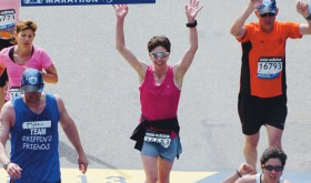 Sarah Ward of Rangely (pink shirt with sunglasses) crosses the finish line with an unofficial time of 4:03.16 and an official time of 3:57.46. She finished the race several minutes before two bombs detonated near the finish. She was five blocks away at the time and described booms that sounded like thunder.