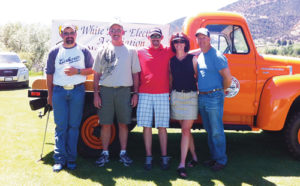 Jason Purkey, Sam Hale, Danny Garcia, Mindy Burke and Todd Morris, pictured in front of an antique White River Electric Association line truck, won a putt-off to win the 29th annual WREA golf tournament on Friday at Meeker Golf Course.