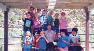 The 2013 Junior Rangers class from the College for Kids in Rangely, led by Ranger Jennifer Walgrave, center, show off new patches at the East Four Mile Draw Site in the Canyon Pintado National Historic District.