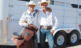 "Incoming CNCC freshman Wade ""Whiplash"" Grimshaw poses with his SSIR All-Around-Cowboy saddle, buckle and horse trailer standing next to CNCC rodeo coach Jed Moore."