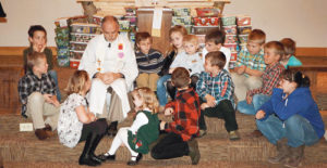 Pastor Jon at United Methodist Church in Meeker sits with some of the children who helped fill 169 local Samaritan's Purse gift-filled shoeboxes that will be distributed around the world as part of a project to bring Christmas presents to children who have never received a gift.