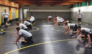 "Meeker High School wrestling coach J.C. Watt, standing left, is excited about having a full wrestling room, which includes several grapplers with varsity experience, six state qualifiers, three state placers, including one state champion, a new assistant coach and five volunteer assistants. ""Everyone will improve because of it,"" coach Watt said."