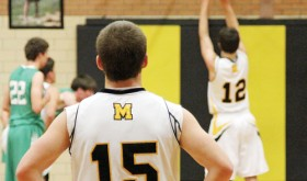 Meeker senior Dylan Mobley (15) looks on as fellow senior Jeremy Musgrave (12) takes a free throw.