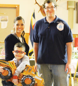 Mom Marisela Preciado and Elks member Cody Reed stand with Preciado's 7-year-old son, Xavier, whose name was drawn for one of the large prizes at the Elks Children's Christmas Party on Dec. 21. Between personal and business donations and the Elks Club's own contributions, approximately $2,500 goes into hosting the party each year. The entire operation, including the food and gifts, costs about $8,000.