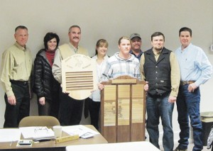 Student Chevy Mohr, at podium, and industrial arts and technology teacher Zach Clatterbaugh presented two wood name-plate plaques, one for current MSD board members and one for past MSD board members. Clatterbaugh said Mohr designed and built the plaques, including engraving the metal plates. In the back row, from left, are current board members Dan Chinn, Mindy Burke, Bill deVergie, Marnell Bradfield, Bud Ridings, Kurt Blunt and Todd Shults.