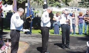 With the Meeker VFW's Honor Guard behind them, from left, Meeker veterans Rob Baughman, David Cole and Pete Kiser removed their caps and lowered their heads to pray for the men and women who, over the history of these United States, gave up their lives while in service to the United States of America while in the military.