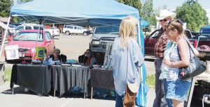 Donna Noller of Meeker, seated left, had one of the more than a dozen arts and crafts booths set up on the street between Meeker Town Park and Circle Park on Saturday as part of the Second Annual Meekerpalooza and Arts and Crafts Fair. Her visitors, above, were from Arizona. The fair ran from 10 a.m. to 10 p.m. with food, art and live bands featured.