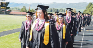 Members of the graduating class made their way across the track at Starbuck Stadium on the way to their seats prior to the commencement exercises.
