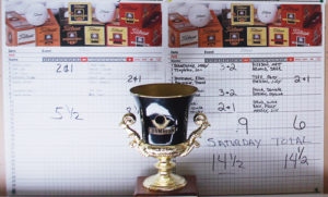 The Rio Blanco County Cup is displayed in front of the score sheets, which document the closest contest in eight years of play between golfers Meeker and Cedar Ridges Golf Course in Rangely. Rangely displayed the cup for a year but have yet to win in Meeker, which is where the 2014 tournament was played and where the cup will remain until next year.