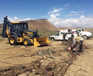County workers cut cable excavated from an illegal dump site in Gillam Draw, southeast of Rangely. The Bureau of Land Management and the Rio Blanco County Road and Bridge Department worked together to remove more than a dozen dump truck loads from the ravine and a nearby shooting range last week.