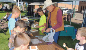 """Colorado saddle maker Bob Klenda spent much of Saturday's """"50 Years Wild"""" celebration in downtown Meeker working with children and showing how he works. He is seen here helping the kids learn to stamp patterns onto leather."""