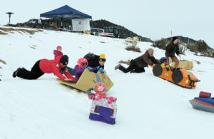 A group of racers in their cardboard sleds get  a push at the starting line on Saturday morning at Paintbrush Park as part of the events Friday and Saturday sponsored by the ERBM Recreation and Park District. There were several classifications of racers during the event.