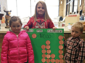 "Parkview Elementary School kindergartener Brielle Lucero, fourth-grader Kenzie Varner and kindergartener Zane Wiley hold up a graph showing each grade's contributions to the ""Pennies for Parkview"" fundraiser, which will raise money for local breakfast and after-school programs until Spring Break. The schools raised more than $230 in the first week."