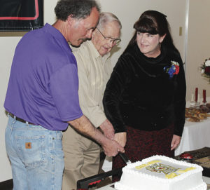 At the Meeker Volunteer Fire and Rescue Banquet on Saturday night at the Fairfield Center in Meeker, a cake-cutting ceremony was held for the oldest and newest members of the department. Dale Frisby, center, and Francis Sullivan (not pictured) are the longest-standing members with the same starting date, and Mark Rogers, left, and Carrie Cook are the newest members, starting in 2015.