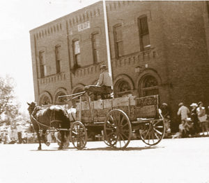 Horse-drawn wagon passes in front of the IOOF building.