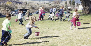 Meeker children launch toward Easter eggs scattered around the area during the annual hunt.
