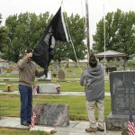 As part of the Rangely observance of Memorial Day on Monday, Pastor Mark Futch and Frank England raised the Prisoner of War flag at Rangely Cemetery as several onlookers watched.