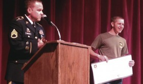 Logan Kinnamon, right, a senior at Meeker High School, holds a demonstration U.S. Army check for $61,812, representing the Montgomery GI Bill money Kinnamon will receive for continuing education once he leaves the Army. The check was presented by Staff Sgt. Scott Mackay, MHS's special Army representative. The check presentation earned a standing ovation at the May 11 MHS awards assembly.
