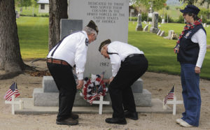 Bob Blevins, right, and Peter Kiser, left, lay a wreath upon the memorial to fallen members of the Meeker community during the Memorial Day observance held at Highland Cemetery on Monday morning. To the right is VFW Ladies Auxiliary member Dawn Jastrem, who assisted by carrying the wreath at both services on Monday. A good crowd gathered at the cemetery to observe the ceremony honoring those who gave their lives while in the Armed Forces in service to the United States.
