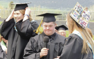 Marcus Archuleta, center, one of the graduating members of the Meeker Class of 2015, is assisted by Reagan Pearce, left, and Brittany Smith, right, as he gets ready to tell the class to turn their tassels, a symbol that the members of the senior class were finally considered to have officially graduated.