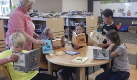 Meeker Elementary School Library received a book donation from the Will James Society. The library was gifted 10 books written by Will James that will be used in the library, available next school year. Some fourth-graders came to look at the books and were very excited to preview them, saying they can't wait to check them out. Above, the kids check out the new books under the watchful eye of school librarian Kay Bivens.