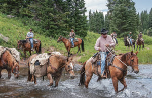Bruce Clatterbaugh of Adams Lodge Outfitters leads a group of veterans on a trail ride across a stream in the Flat Tops northwest of Meeker near Marvine Lake.
